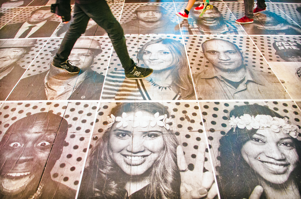 2013.04.24 – New York City, NY – A pedestrian walks over a series of portraits pasted to the sidewalk in Times Square as part of a collaborative art project by photographer JR.