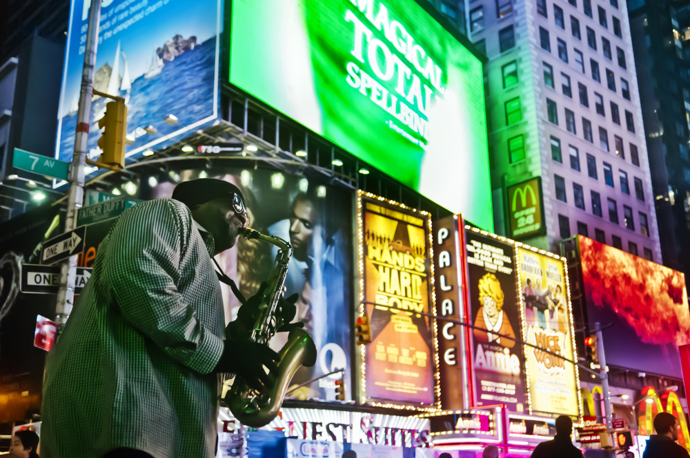 "2013.04.24 – New York City, NY – Street musician Sweet Lew plays on a street corner in Times Square. ""This is my spot since the '80′s,"" he says, ""Before all of this… I was here."""