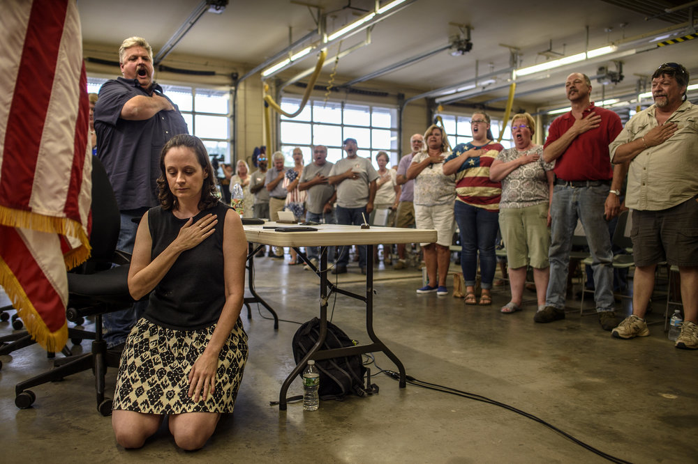 "Haddam, Ct. - 07/30/2018 - Raising their voices for the last line of the pledge of allegiance, ""with liberty and justice for all,"" Haddam selectman Larry Maggi (left) and attendees to the town's board meeting, stand as Haddam Selectwoman Melissa Schlag kneels. Schlag knelt two weeks prior, at the town's July 19 meeting, saying she was protesting Donald Trump in ""extreme sorrow."" Since Trump's election, Republican Maura Wallin of Haddam and Democrat Eric Couture of Killingworth, two members of the Region 17 school board, have been kneeling during the pledge at their board's meetings."