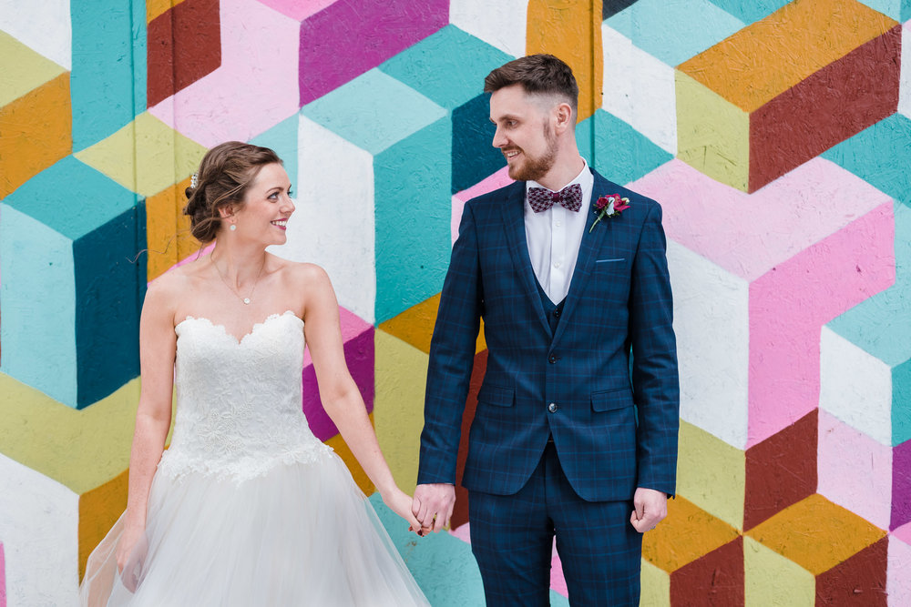 Bride & Groom in front of colourful wall in Belfast Cathedral Quarter