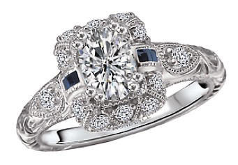 Art Deco styling with an oval center and blue sapphire accents   from   D.J. Bitzan Jewelers.