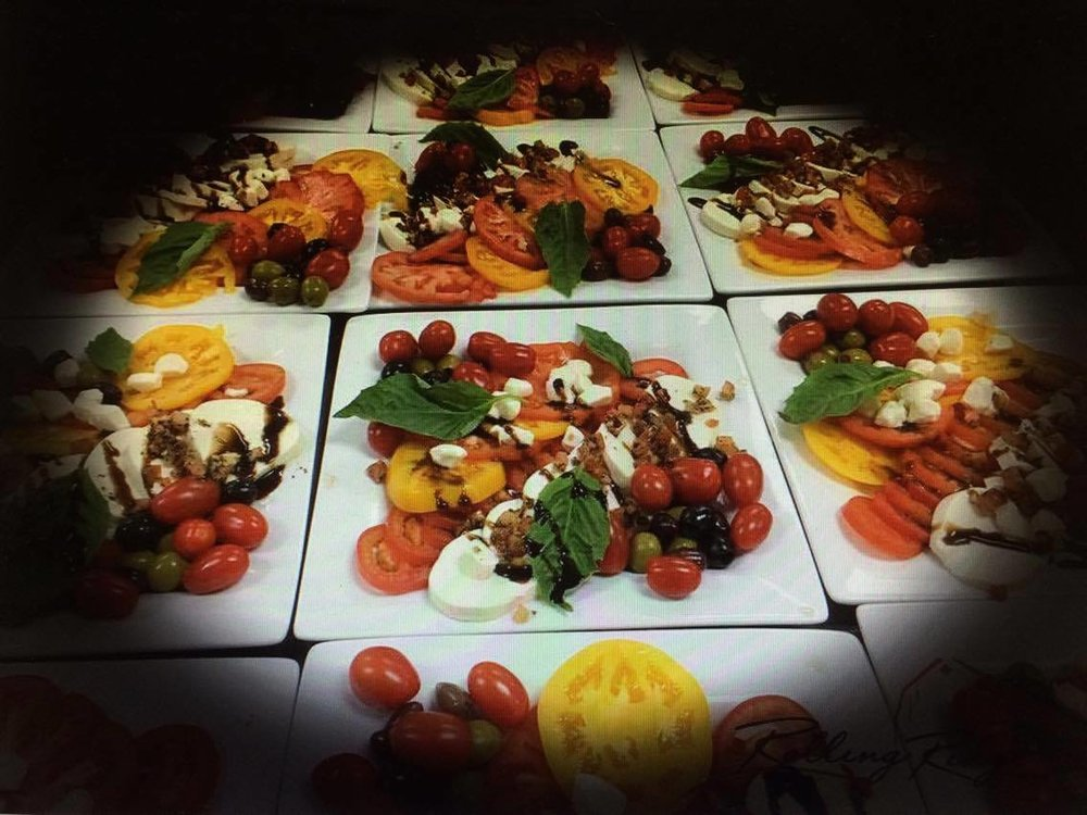 Family Style Caprese Salad with sliced mozzarella, heirloom tomatoes, fresh basil, and a drizzle of balsamic glaze