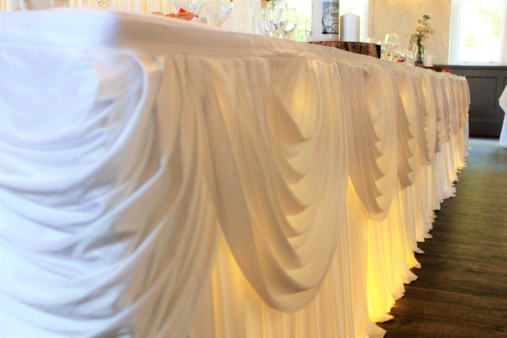 Top table skirts - We have a gorgeous collection of top table, cake and registry table skirts for hire including a range of coloured swags. Enhance the look of your top table from only £70.