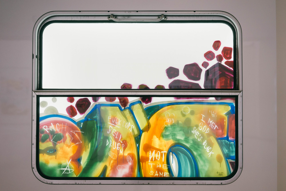 My favorite piece at Pasta Oner's  Las Day in Paradise  exhibition was this train window covered in graffiti. The scratchings are interestingly made from the opposite side. This and other pop culture references in art at www.MarinaSays.com