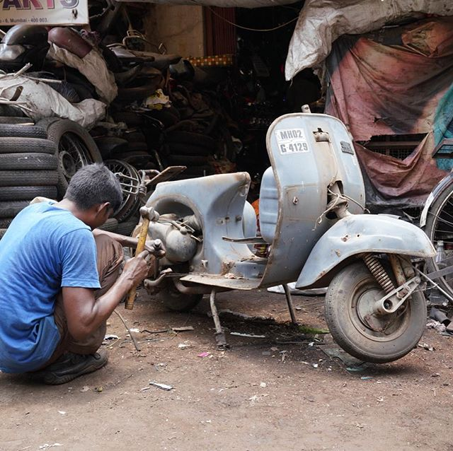 A 🛵 meets it's Destroyer!  A worker goes to it dismantling the scooter for scrap & recycling! #scrap #recycling #vespa #scooter #urbexphotography #street #streetphotography #india #chorbazaar #urbexphotography