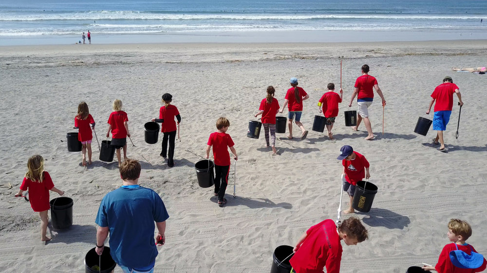 -Beach Cleanup - Connor with Microactivsts storm the beach.jpg