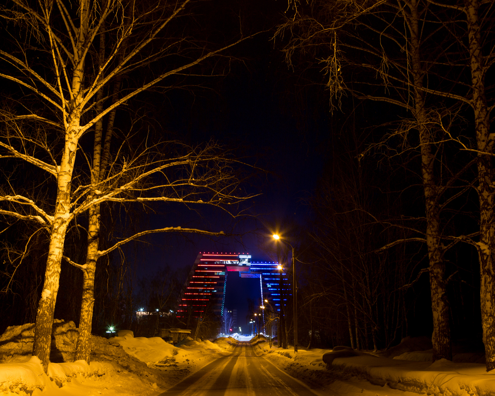 The main building of Akadempark lit up at night in the red, white and blue of the Russian tricolor. The 13-story buildings spans a road and towers over everything else in Akademgorodok. The top floor, accessible via a transparent skybridge, is a dedicated coworking space for tech entrepreneurs.