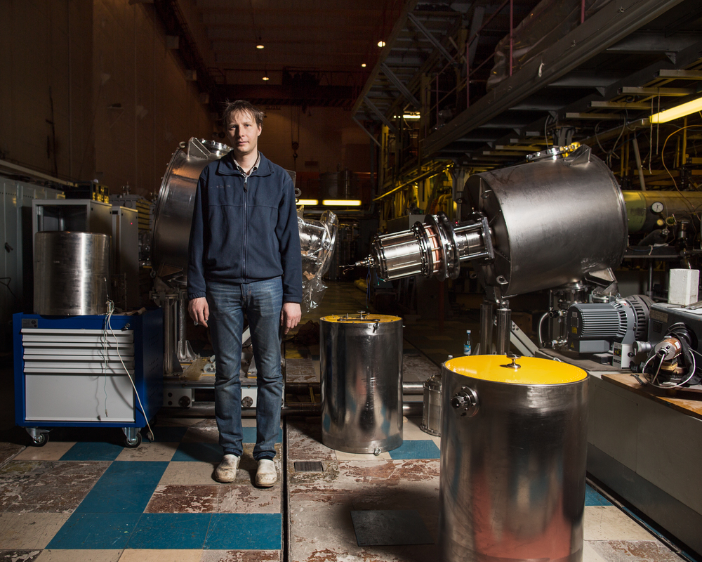 Sergey Polosatkin stands with dissambled pieces of machines that he uses in the study of plasma physics. The machine behind him is a neutron generator.