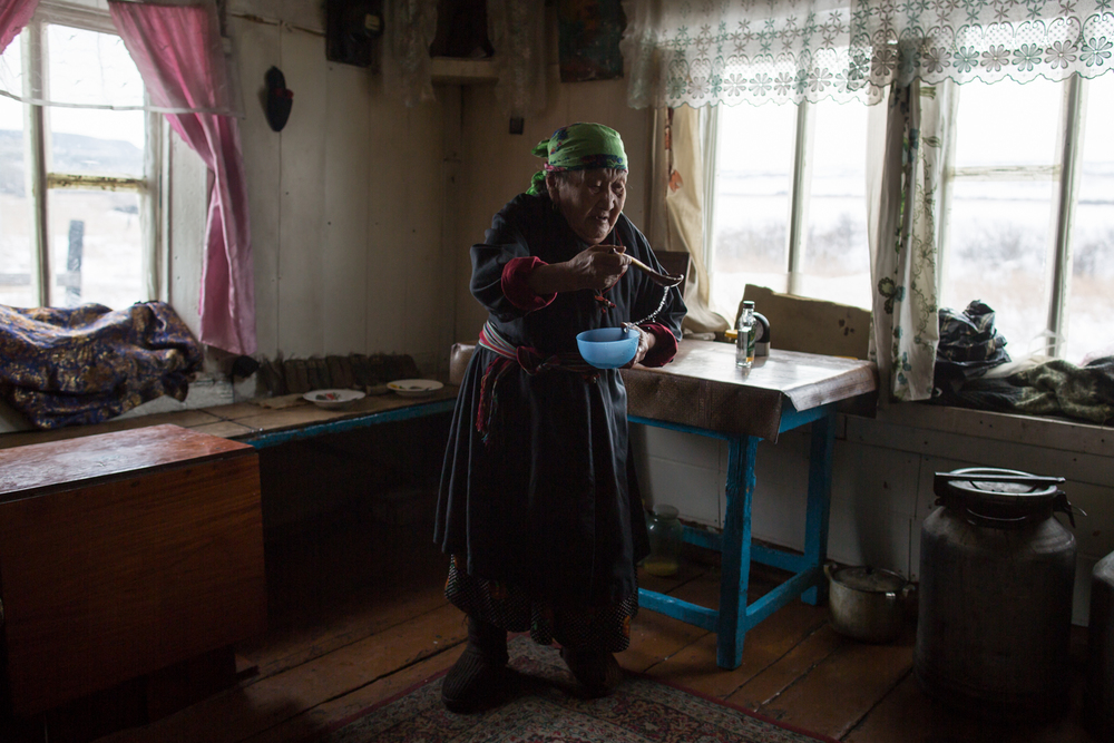 Anna Alagyzova purifies her home with vodka before a ceremony where she will feed a doughy mixture to 12 household gods, dolls called emengeders lined up on the shelf behind her. Alagyzova is one of few remaining members of the Teleut people that speak the people's native language.