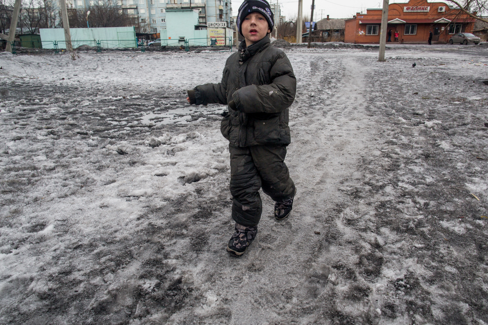 A young boy walks through soot-covered snow in the coal mining town of Leninsk-Kuznetsk in the Kemerovo region.