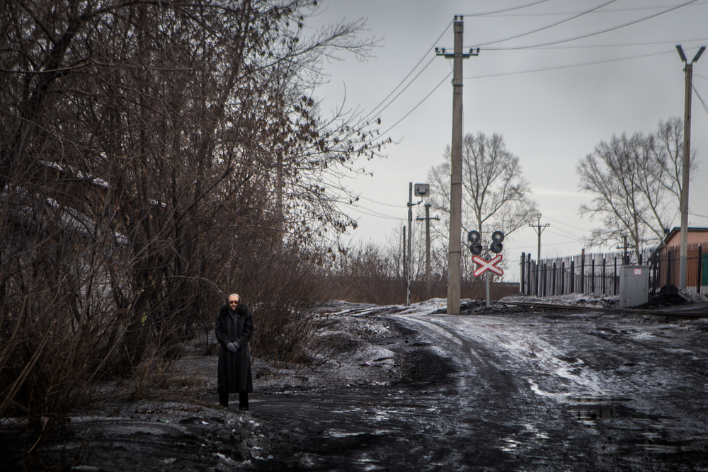 A woman stands near the road, watching, in Leninsk-Kuznetsk.