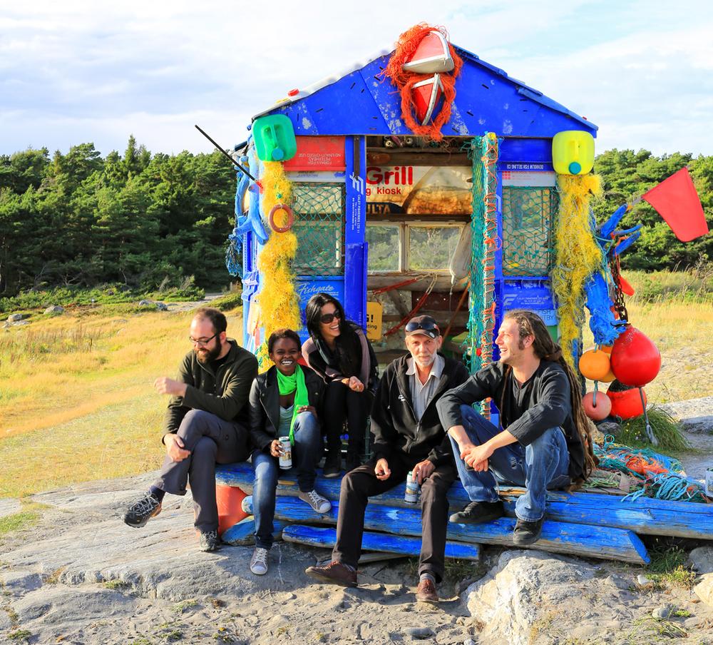 Opplevelser og attraksjoner står i kø for å ta i mot turister til Kirkøy. Her er turister fra Hellas, Kenya, Italia, Polen og Norge samlet ved inngangspartiet til plasthytta  Ocean Hope  på Storesand.