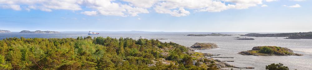 Sverige på andre siden av fjorden. Riksgrensen mellom Norge og Sverige går omtrent midt i fjorden. På høyre side i bildet sees det sydøstre området av Hvaler-øya, Herføl.