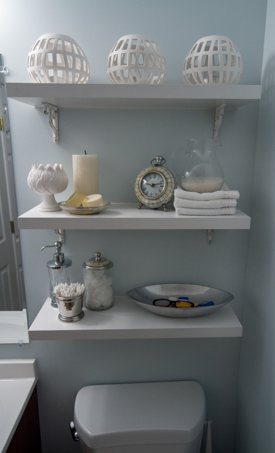 Shelves help utilize vertical space in this small master bathroom