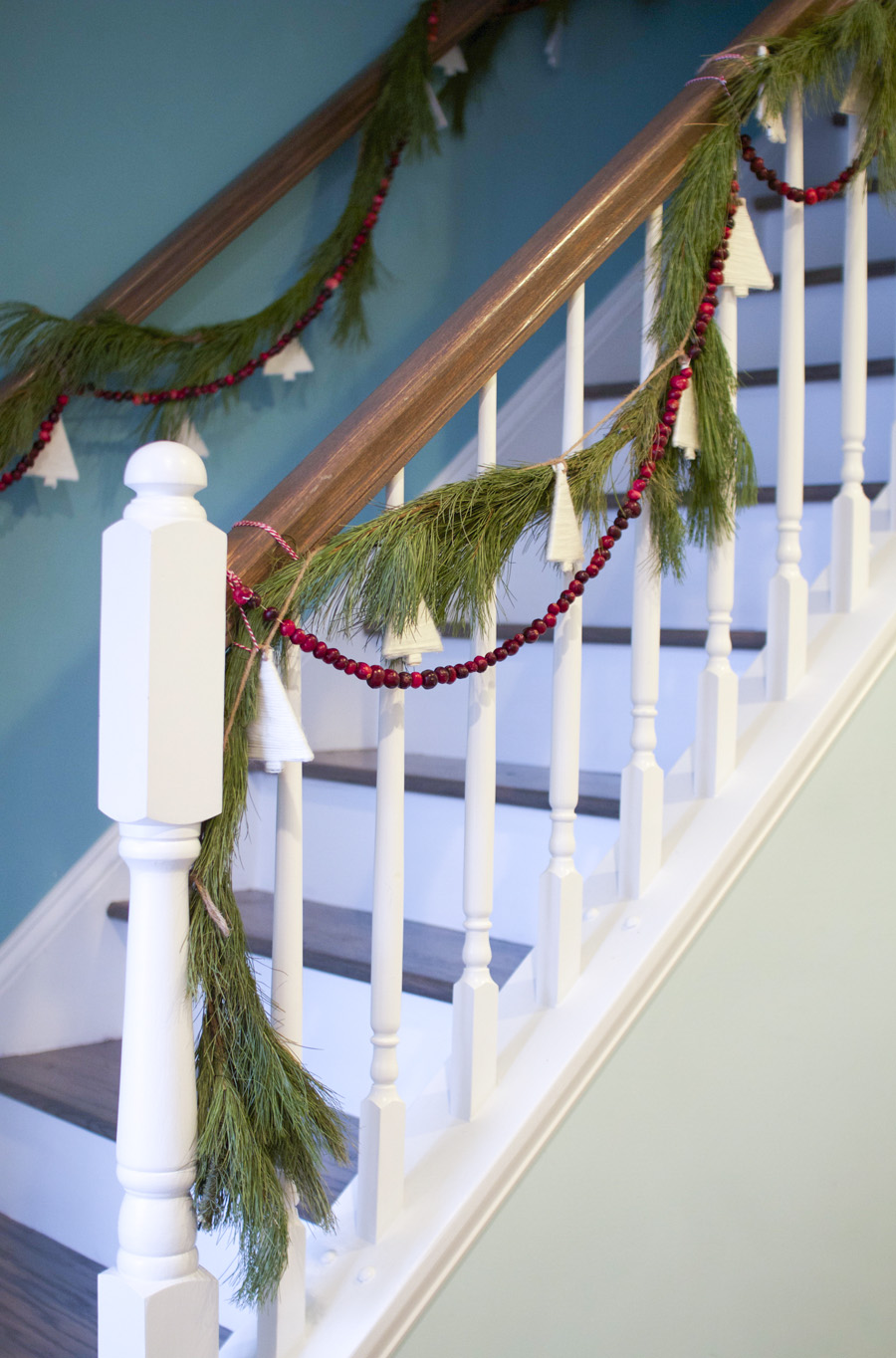 Our Christmassy stairwell, featuring pine, cranberries and white yarn Christmas tree garland.