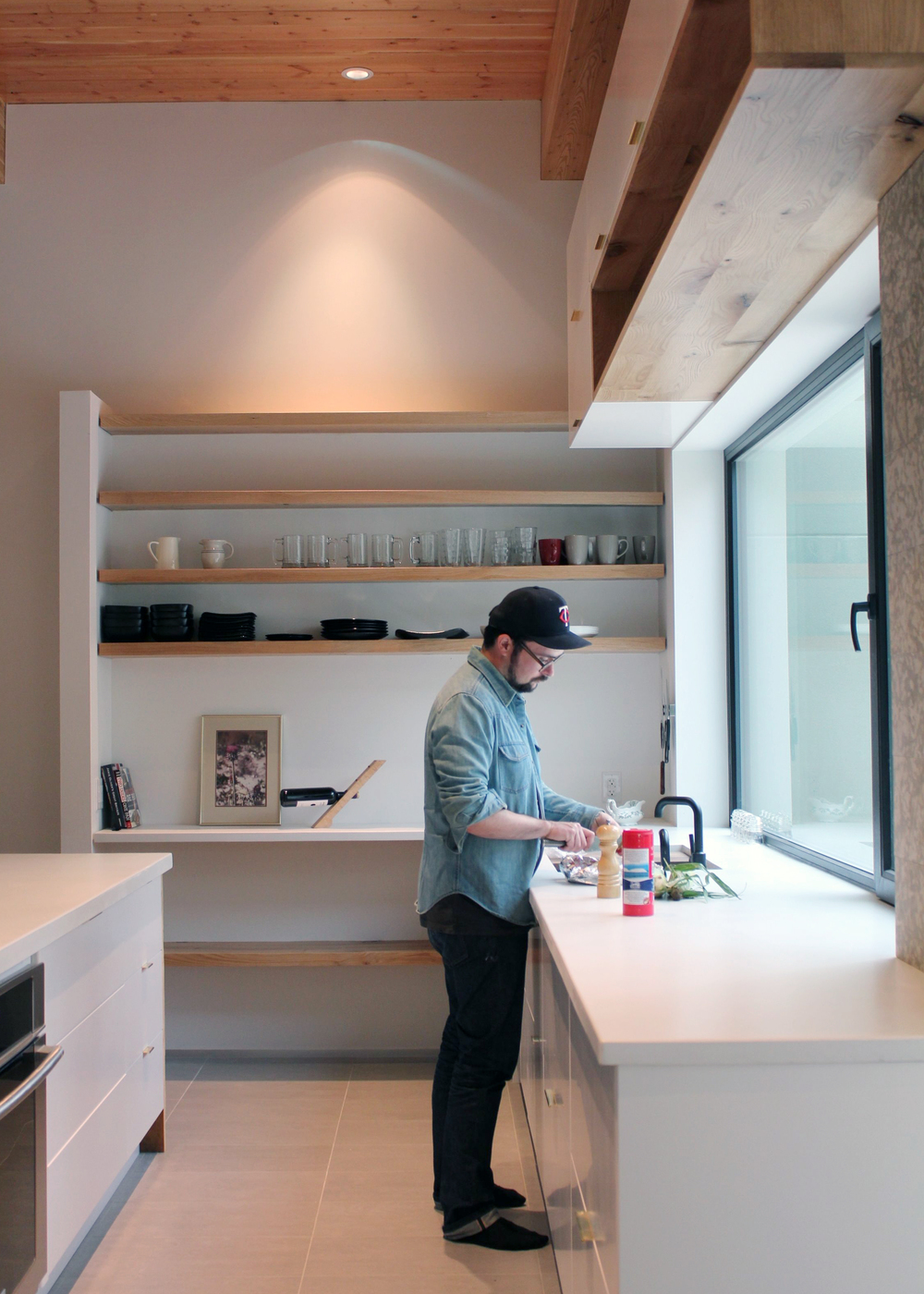 kitchen view with solid wood open shelving, brass drawer pulls and white concrete counter tops