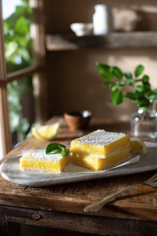 Lemon Bars on a Rustic Farmhouse Table Stock Food Photo