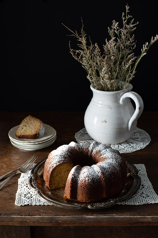 Bundt Cake on a Rustic Farmhouse Table with a Missing Slice in a Dark Setting Stock Food Photo