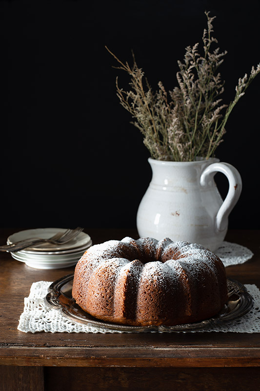 Bundt Cake on a Rustic Farmhouse Table in a Dark and Somber Setting Stock Food Photo