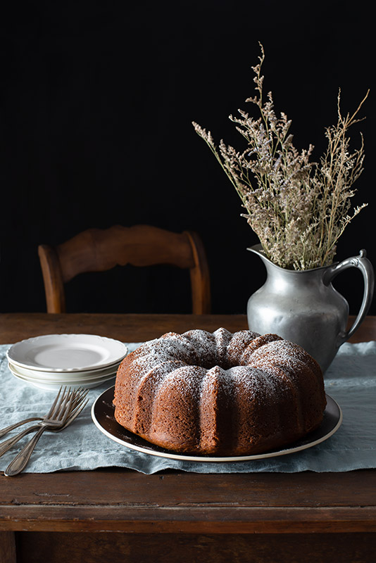 Large Bundt Cake on a Rustic Farmhouse Table in a Dark and Somber Setting Stock Food Photo