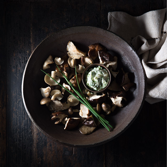Roasted Mushrooms  with Chive Butter on a Rustic Wood Table Stock Food Photo