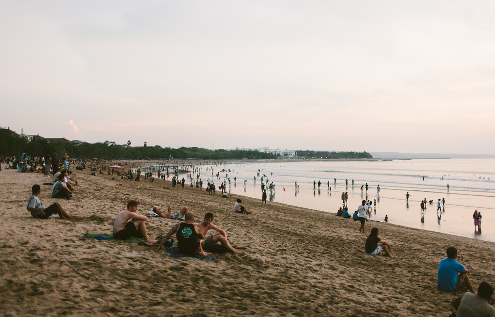 Hundreds of tourists watch the sun set over Kuta Beach, Bali