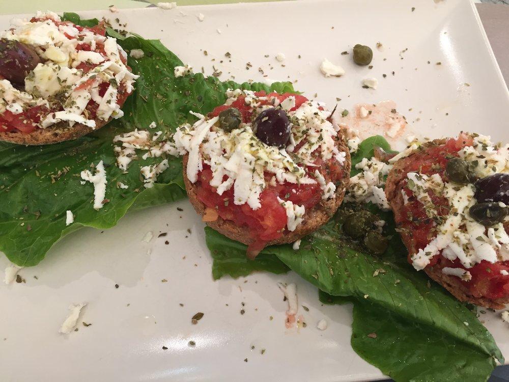Dakos: Cretan meze with soaked barley rusk, chopped tomatoes, and mizithra cheese