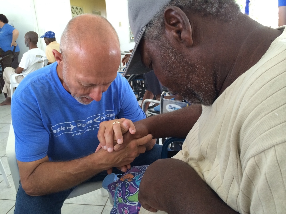 Bob praying with a resident of the Fienne's Institute in Antigua.