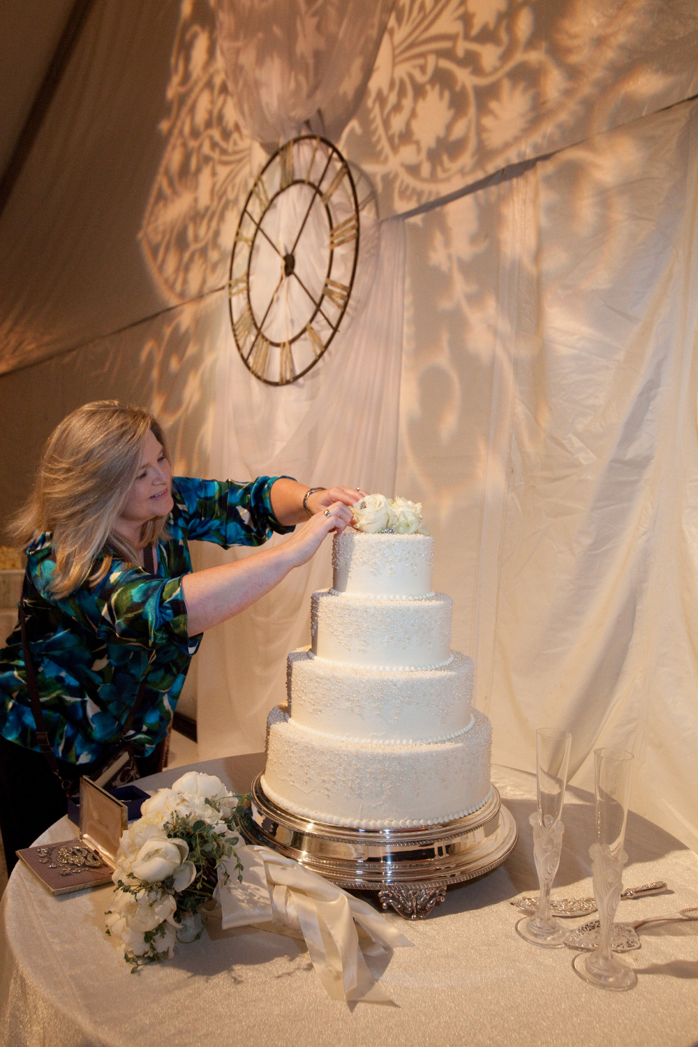 Rachael adding a last minute touch to the cake with family heirloom broaches.  Photo courtesy of  Marsha Perry Photography .