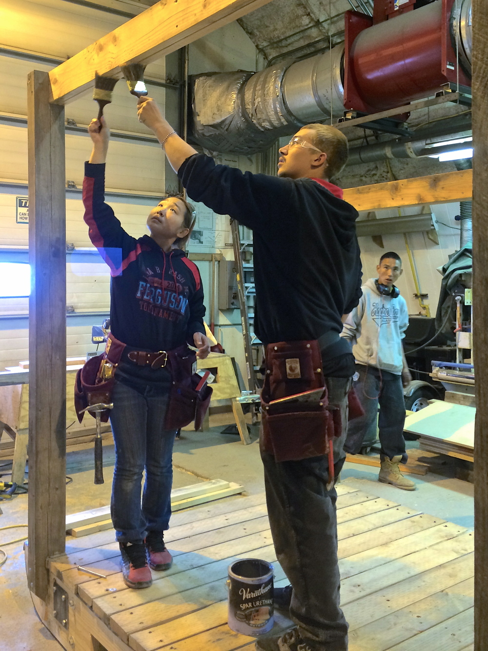 Misha and Branham apply a coat of clear finish to the installed beam.