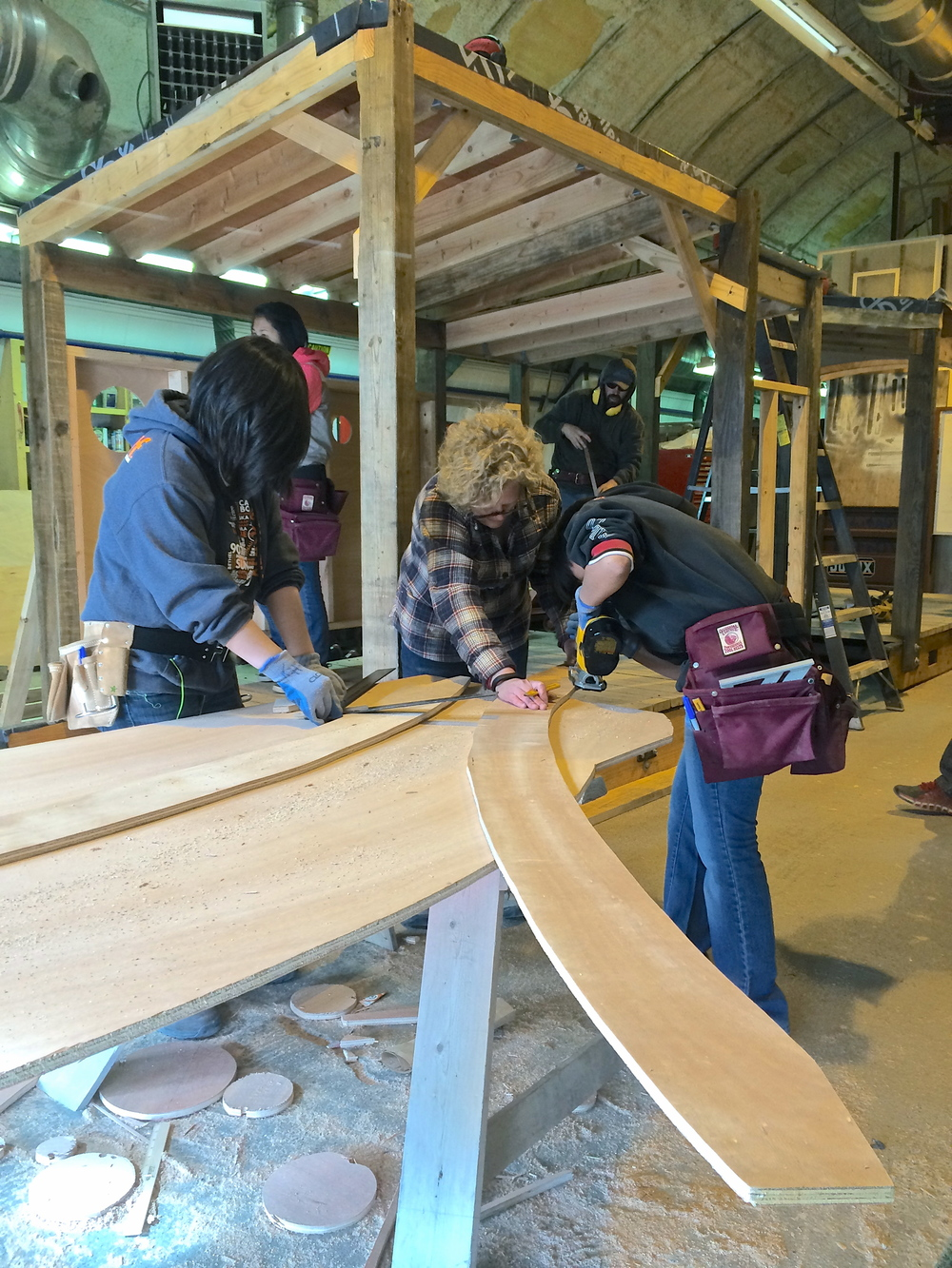 Kirsten, Milly, and Marina work to cut the curved ribs for the wall of A.C.