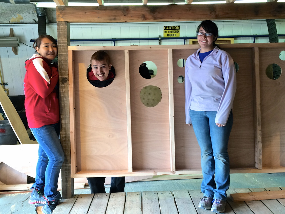 Misha, Branham, and Evelyn pose happily with the wall they framed and cut portholes into.