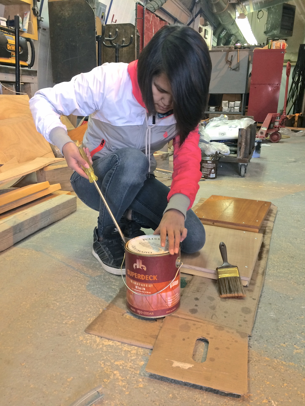 Lena puts a coat of finish on a plaque for each structure.