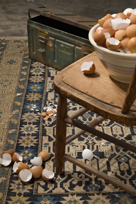 """Detail, """"Empty Shells,"""" one of the installations for """"Sanctuary,"""" shown February 2018 at Gallery 114. Materials include eggs, an old chair, a worn rug, a window (not seen here)and a USMC WWII bomb carrier."""