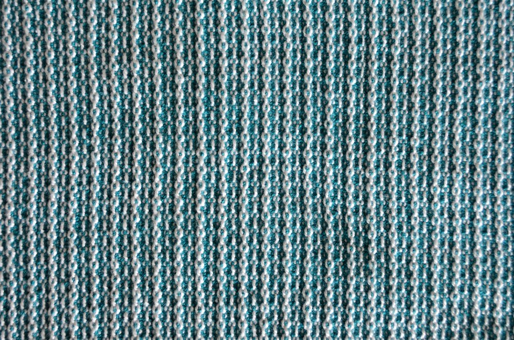 close up on a Queen's Cord in teal and bleach woven towel