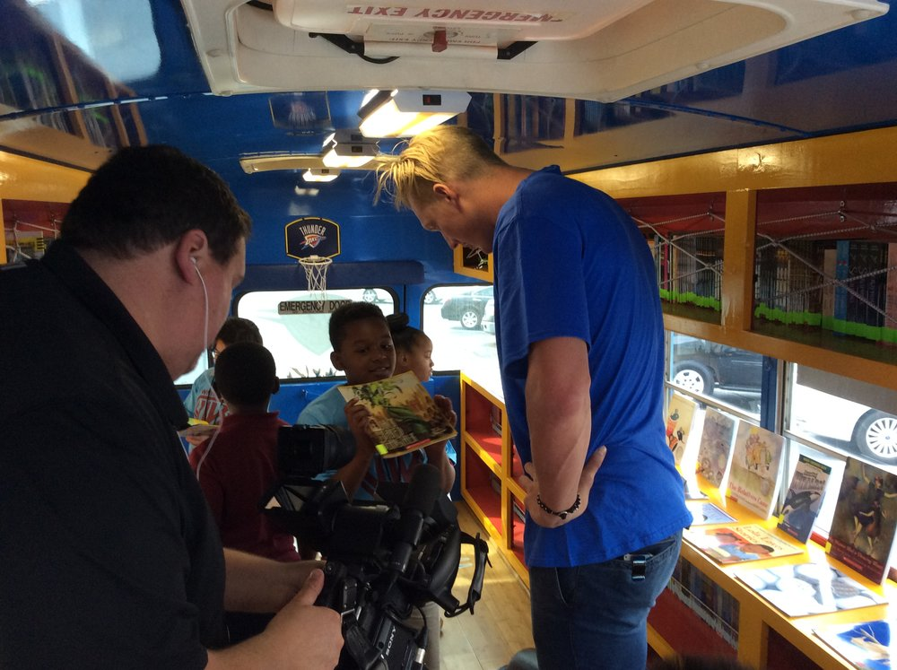 Thunder forward Kyle Singler helps school kids pick out books to read inside the Rolling Thunder Book Bus. (Photo by Randy Renner for InsideThunder.com)