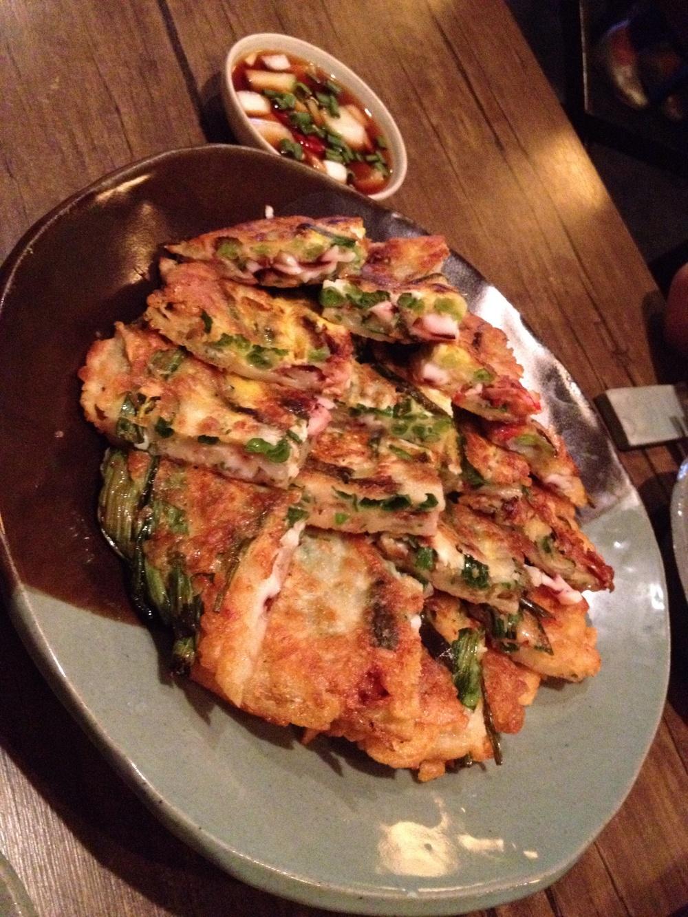 해물파전 (HaeMool PahJun) = Savoury seafood pancake mostly w. squid, shrimp and green onions. Very hot, crispy and delicious! Goes perfect with the soy-sauce w. a bite of onion/green onion each time!