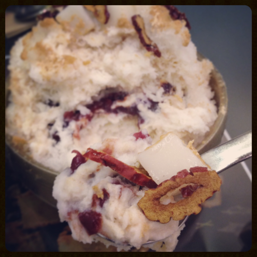 Super soft and flaky milk bingsoo with Misoot Garu (Korean grain powder) sprinkled in and around the shaved ice. Topped with soft, sweet cubes of rice cake, crunchy bits of dried dates and filled in the centre with (팥 - Paht) sweet red bean.