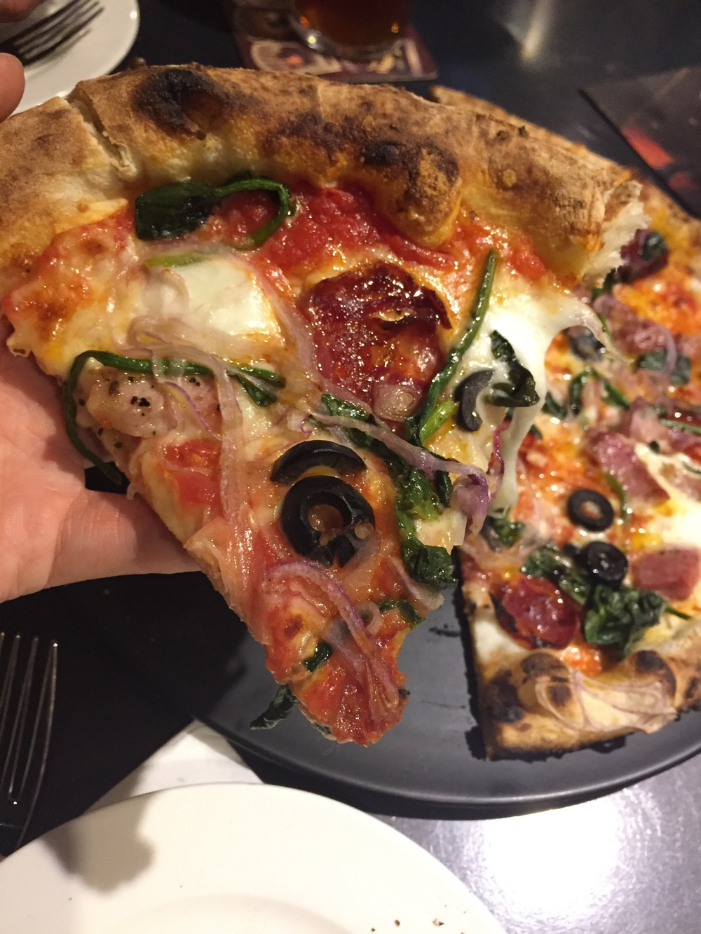 Neapolitan pizza is characterized as having more sauce than cheese, therefore leaving the middle of the pie typically wet or soggy, which is why the sizes are generally smaller, more like a personal pizza size. They are cooked at very high temperatures for more than a minute and a half to get a perfect crispy yet chewy crust with the cheese just bubbling.