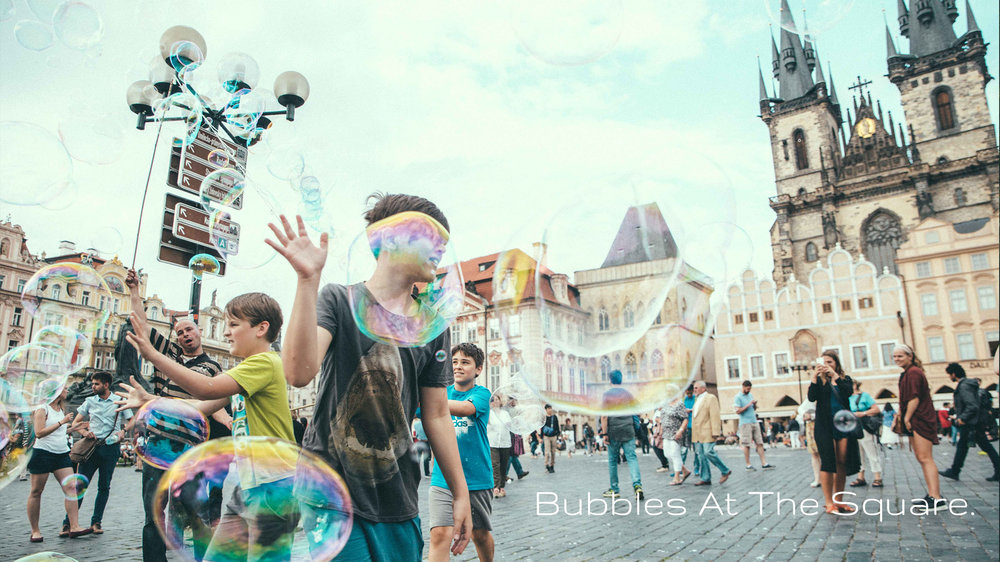Bubbles At The Square. - A chance encounter with a man and his bucket of soap water at Prague's Old Town Square brightens the day of children and their parents alike on a lovely Summer evening.Click on image to enter.