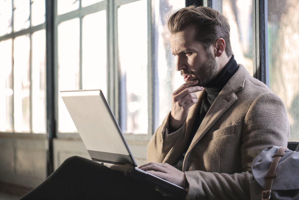 Image of man at laptop looking confused