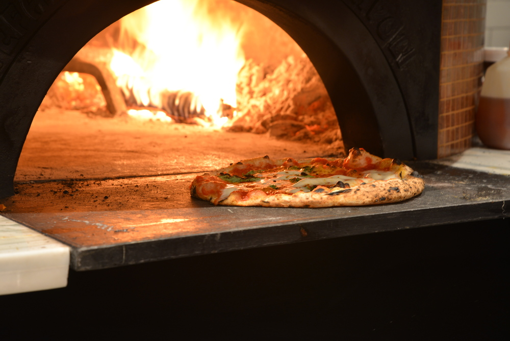 A wood-fired oven that hits nearly 1,000 degrees cooks Settebello's pizzas fast./ HEATHER GOLDIN, STAFF