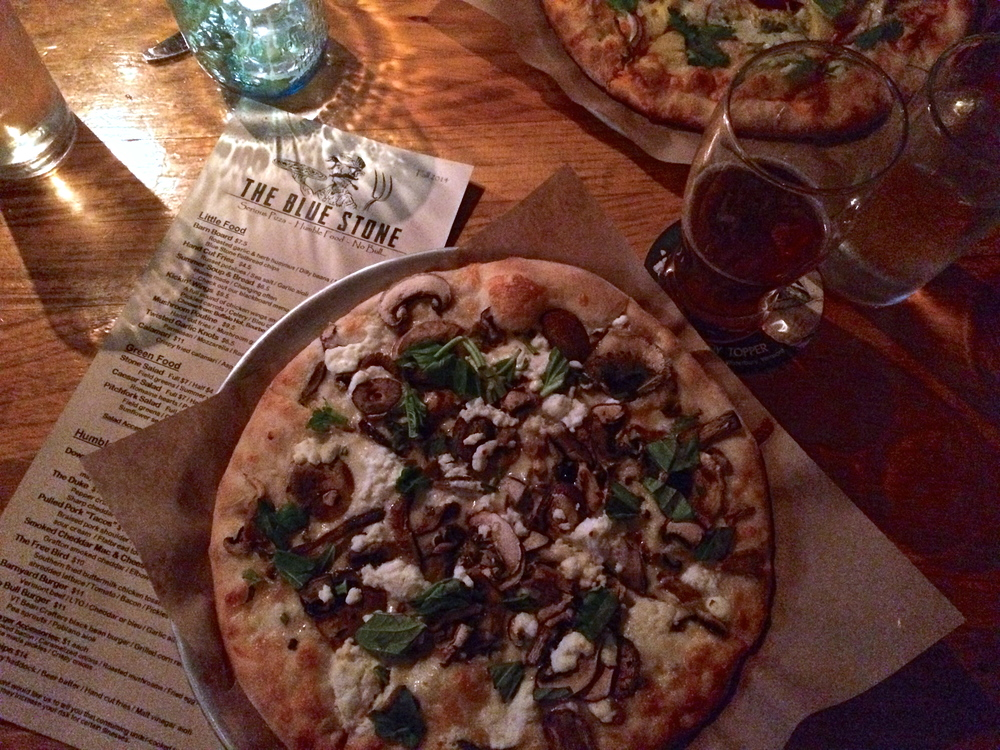 The Blue Stone Pizzeria in Waterbury, VT. Local beer, local produce, fresh wood-fired pizza... perfection. There's three different kinds of mushrooms, local goat cheese and basil on that glorious pizza! Switchback to wash it all down.
