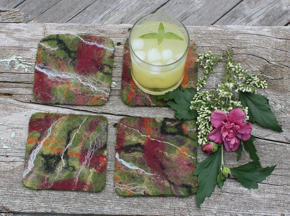 "Reversible coasters, 4.5"" square(ish), wet-felted of wool and silk fibres. The reverse side is a plain leaf green.  $29.00. To purchase, click on photo."