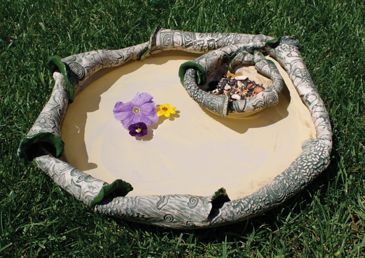 "This very organic bird bath has a built in seed bowl so birds can ""Dine, Dip and Dash"". A creamy glossy glaze inside and textured stained bottom curled up around the edge up into the bowl. SOLD."