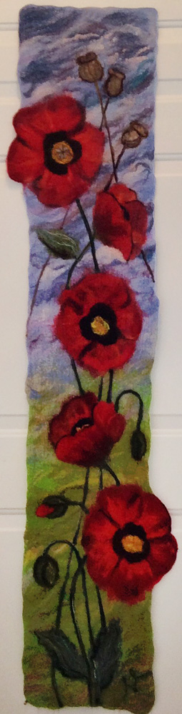"This felted tapestry of poppies will go with ceramic pieces I've made for a curated exhibition at the Art Gallery of Burlington in April 2015. The ceramic pieces are 4 poppy seed heads and a small box with a sliding lid, made to look like wood, filled with some actual poppy seeds. The piece was inspired by a line in a poem by Marilyn Gear Pilling. The poem talks about the loss of Marilyn's niece to suicide and her trying to understand why. The line is: She asks the poppy and it gives her a small box of black seeds. I was hoping to convey the circle of life. From seeds to buds and flowers, to seed heads and back to seeds. The poppy has no answers but offers that out of death comes the hope of new life. This piece is 12"" wide by 61"" long. $1500.00"