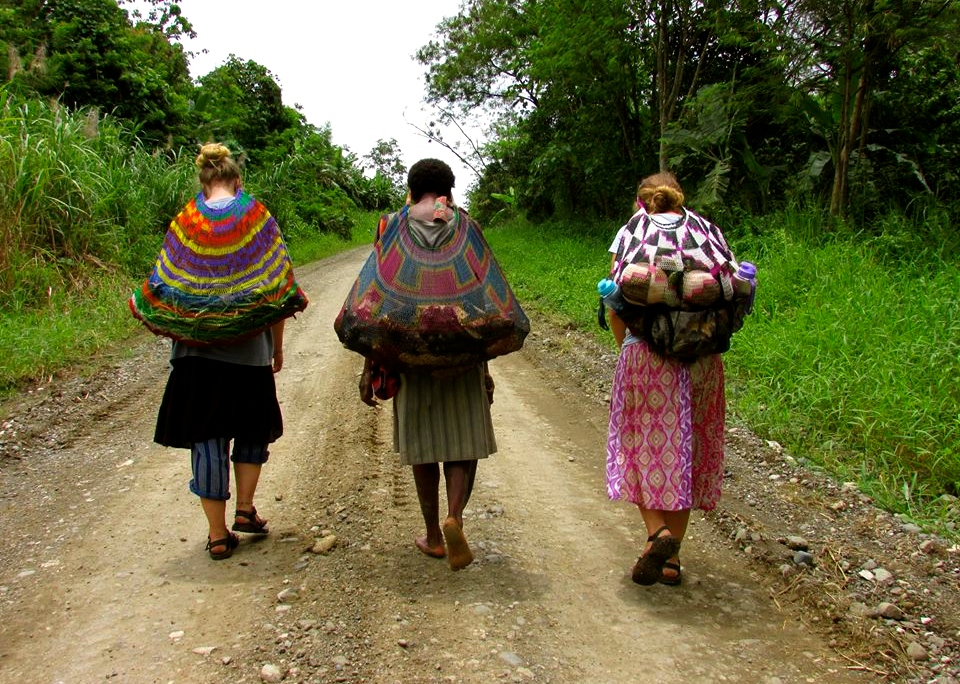 Gabriele, Wasmama (watch mama), and Stephanie bring back food from the garden in their bilum bags. The belum is used to carry all sorts of things from food to babies, and you carry it on your head!