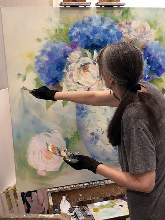 Artist Laurie Pace in progress painting of flowers.jpg