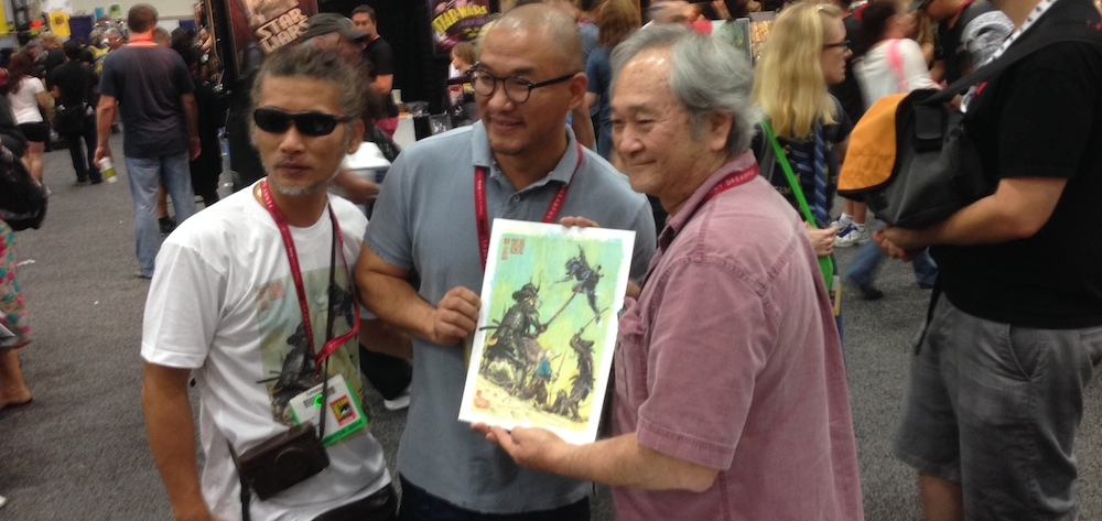 r. to l.: Stan with Kim Jung Gi and one of Kim's collaborators, posing with the original art used for the limited-run San Diego Comic-Con shirt