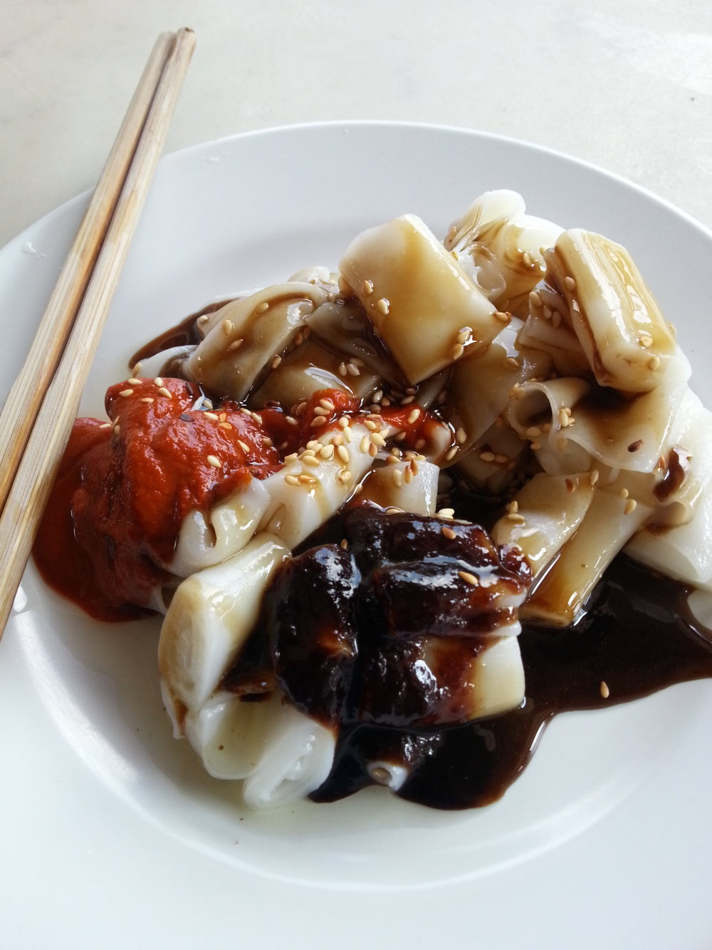 Chee Cheong Fun is flat rice noodles served with sweet, tangy, sour and soy sauces. You'll find this dish in Hong Kong and Kuala Lumpur as well, but in Penang we like to do it a little bit differently. The local version is served with thick sauces that includes either a sweet chili sauce or a spicy sambal. This place is just around the corner from Chowrasta Market, on Lebuh Kimberley.